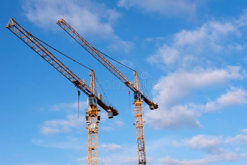 Two yellow construction cranes against blue sky with a few cloud stock photography