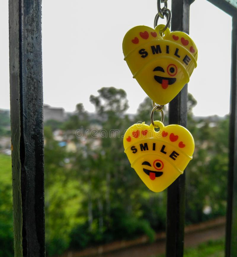 Two yellow hearts keychains, smile, balcony, natural background stock photography