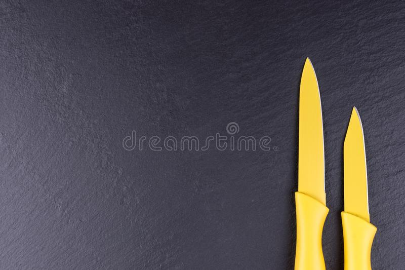 Two yellow kitchen knives on black slate plate. Two yellow kitchen knives isolated on black slate plate stock photos