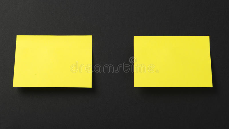 Two yellow post-it on black background. Copy space stock photo