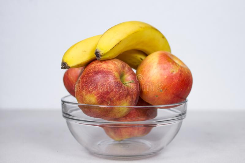 Two Bananas And Four Apples in Glass Bowl Isolated Composition on White Background stock image