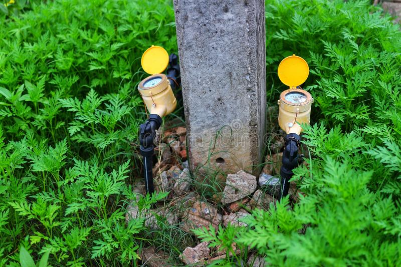 Two yellow water meters between the pillars  Green tree background  Water supply concept royalty free stock photo
