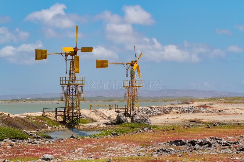 Two yellow windmills near water on Bonaire stock photography