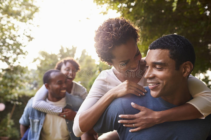 Two young adult black couples having fun piggybacking royalty free stock photo
