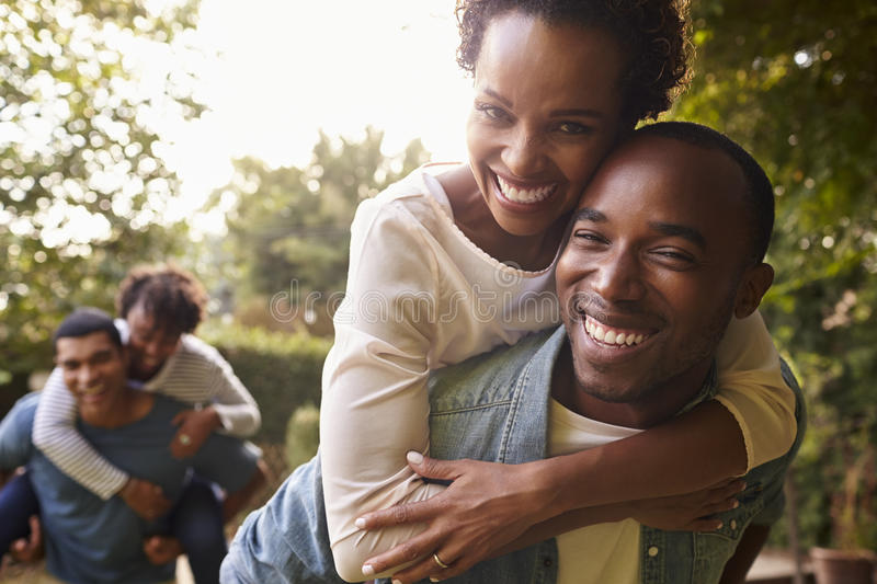 Two young adult black couples piggybacking look to camera stock image