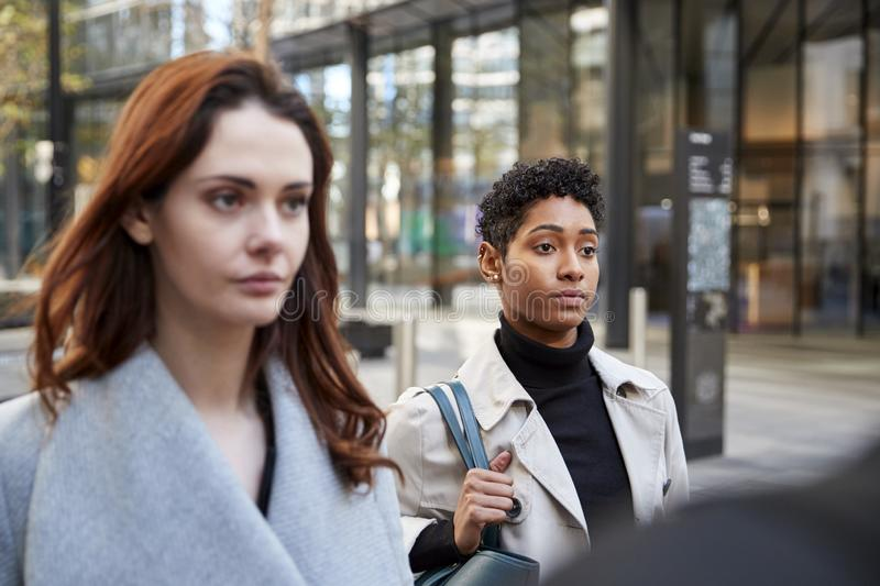 Two young adult businesswomen walking in the city of London, close up, selective focus royalty free stock image