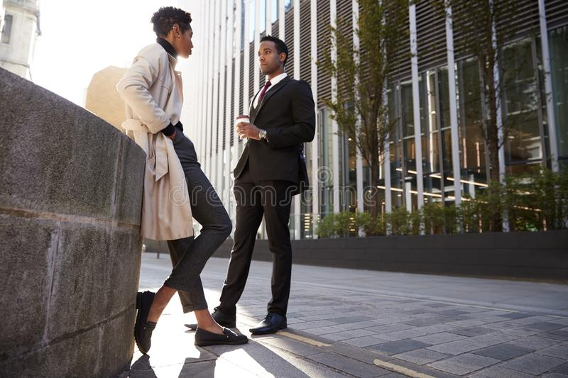 Two young adult colleagues standing on the street talking, low angle royalty free stock photography