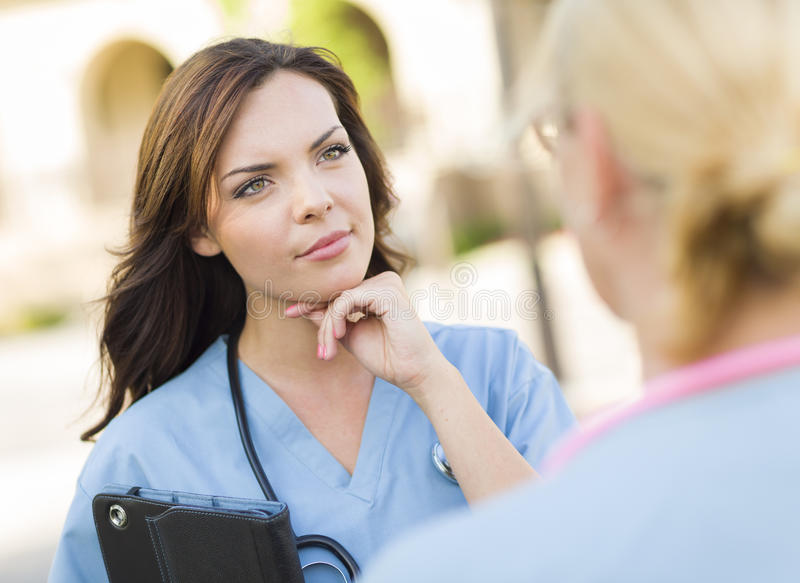Two Young Adult Female Doctors or Nuses Talking Outside royalty free stock images