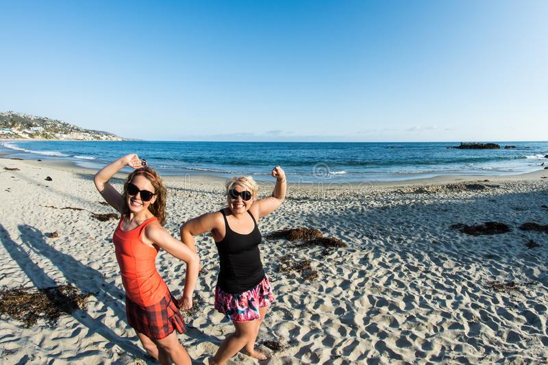 Two young adult female friends show off muscles at a California Beach on a sunny day. Fisheye lens view stock photo