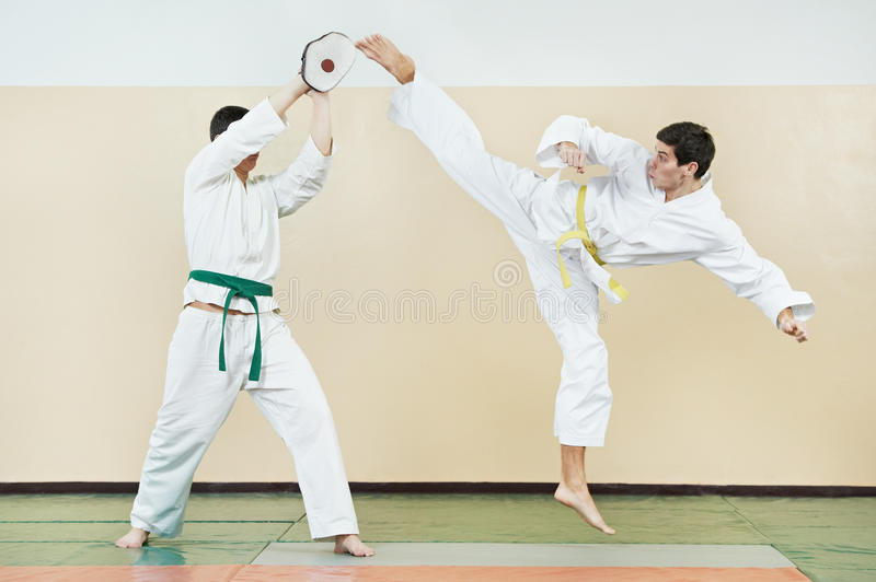Two man at taekwondo exercises. Two young adult people in kimono training taekwondo martial art at gym royalty free stock photo