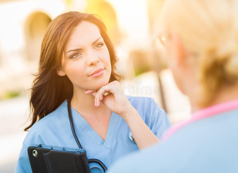 Two Young Adult Professional Female Doctors or Nurses Talking Outside. stock photos