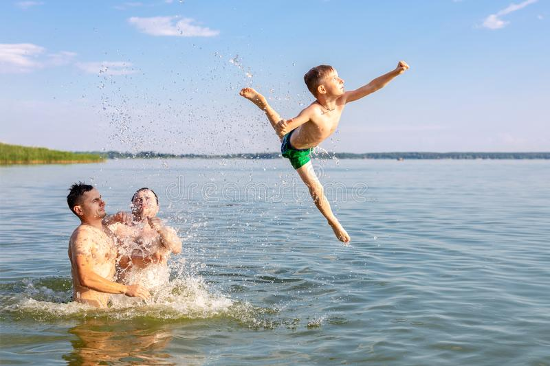 Two young adults and one kid boy having fun in river or lake. Child jumping high with help of friends. Summer outdoor activity and royalty free stock image