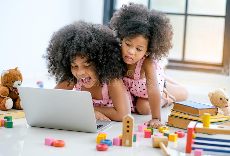 Two young African girls play with notebook computer among toys, doll and book in front of glass window.  stock image