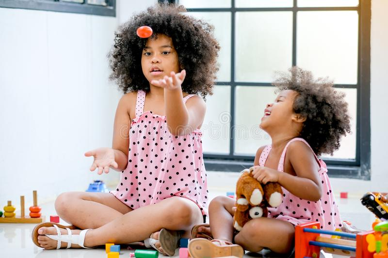 Two young African girls play together that older throw some toys and younger girl look fun with the activity.  stock image