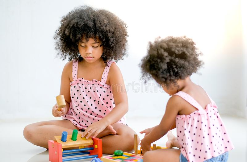 Two young African girls play toys together with main focus on left side girl who look concentrate with her toys.  stock image