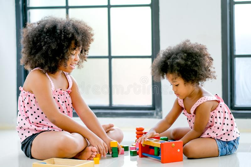 Two young African girls play toys together with main focus on right side girl who look concentrate with her toys.  stock photo