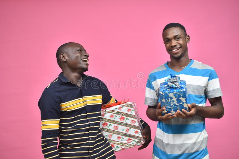 two young african men holding presents stock photos