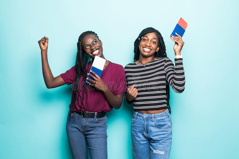 Two young african women with flight tickets ready for travel isolated on pastel blue background royalty free stock image