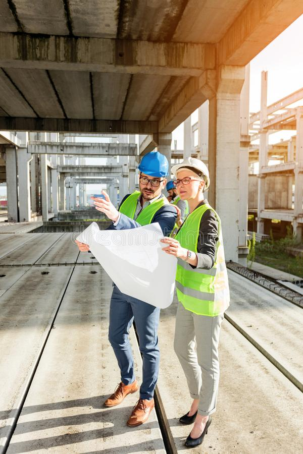 Two young architects visiting large construction site, looking at floor plans stock photography