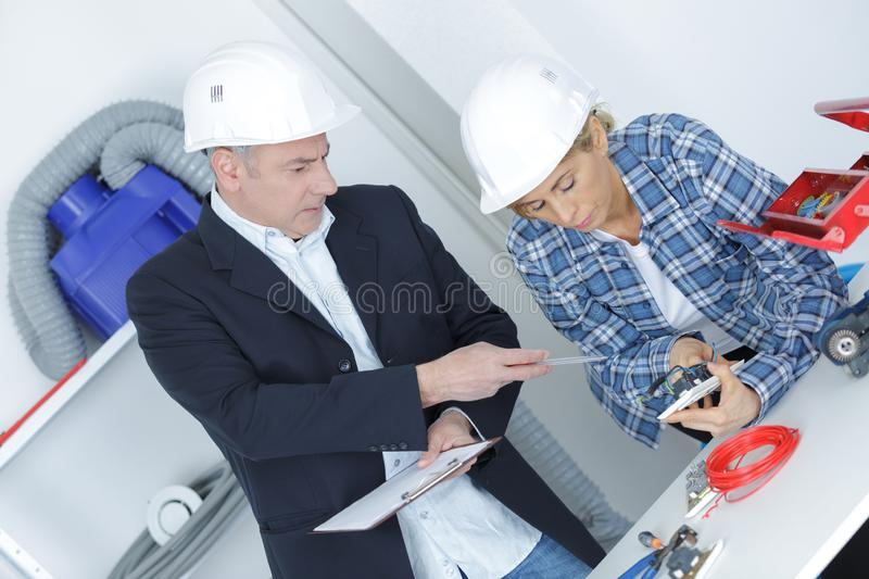 Two young architects discuss about construction plan. Plan stock photos