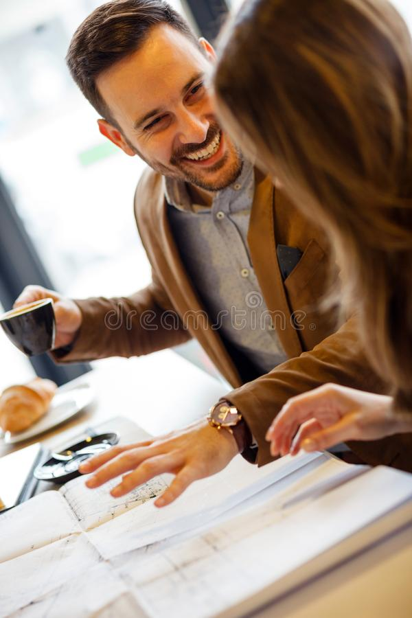 Two young architects discussing building plans during a meeting in a modern cafe royalty free stock images
