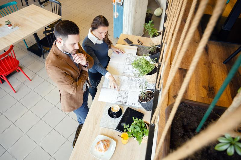 Two young architects looking over building plans during a meeting in a modern cafe royalty free stock image