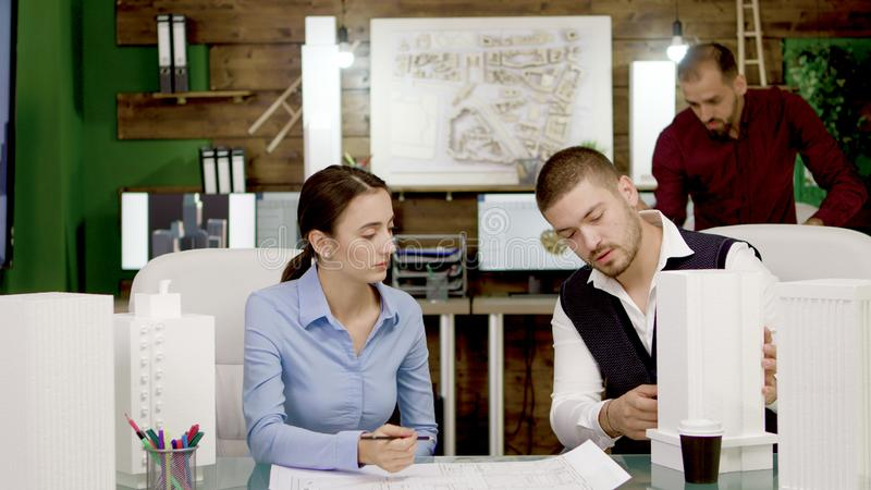 Two young architects working on urban plan for office buildings royalty free stock photos