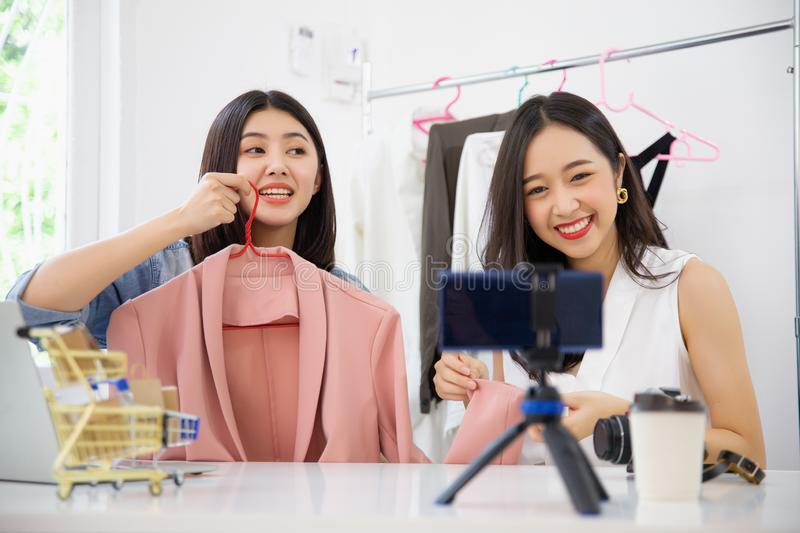 Two young asian attractive woman vloggers sitting in home present cloth dress online business shop online ideas concept. royalty free stock photo