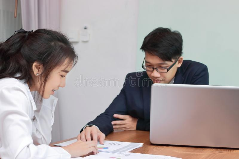 Two young Asian business people analyzing paper work or charts together in modern office. Team work business concept. Selective fo royalty free stock image