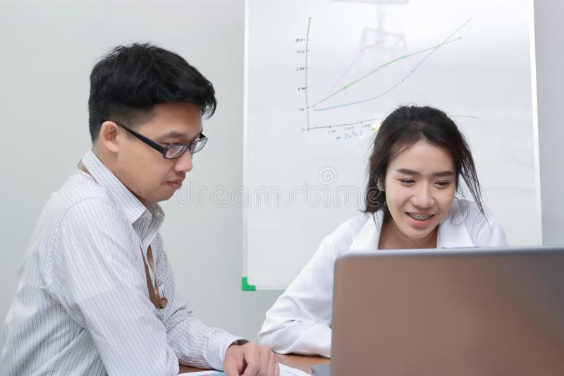Two young Asian business people working with laptop together in modern office. Team work business concept. Selective focus and sha royalty free stock images