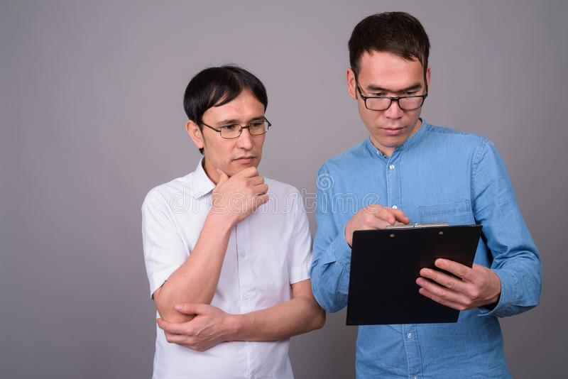 Two young Asian businessmen wearing eyeglasses together against stock images