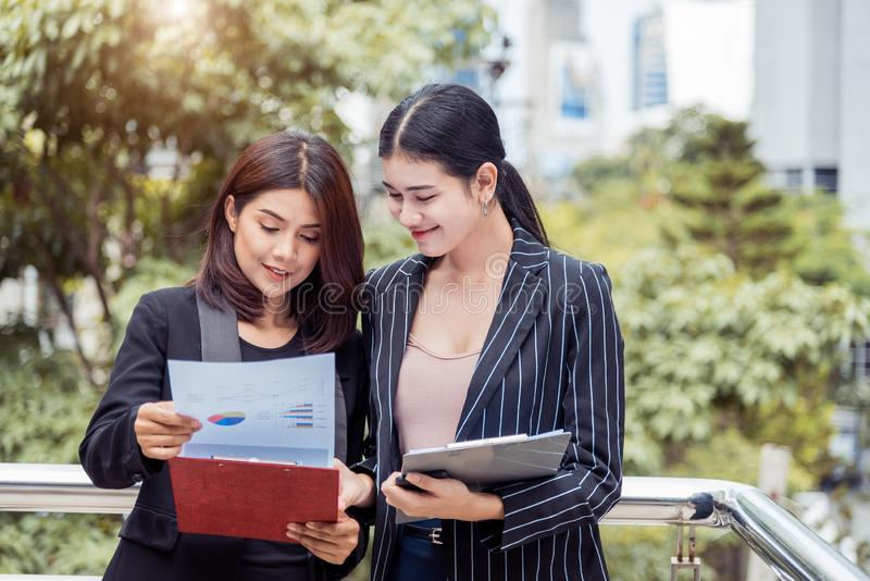 Two young Asian businesswomen looking into document file folder for analyzing profit or sale break even point after marketing. stock images
