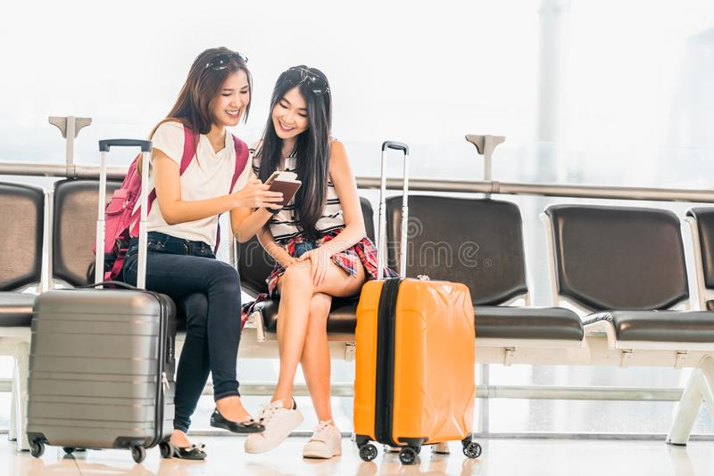 Two young Asian girl using smartphone check flight or web check-in, sit at airport waiting seat together. Air travel lifestyle, exciting summer vacation trip royalty free stock image