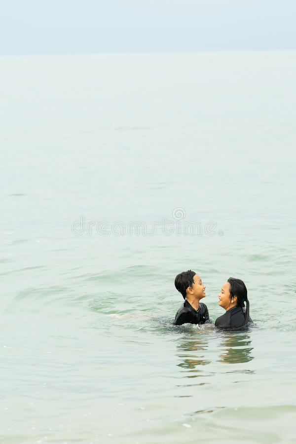 Two young asian kids are swimming in the sea royalty free stock image
