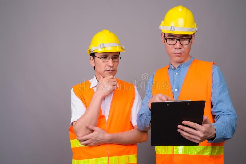 Two young Asian men construction worker together against gray ba stock photography