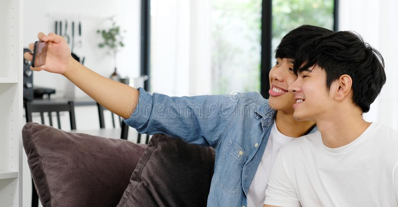 Two young asian men friend taking photo together, asia gay couple selfie with phone while sitting in home living room, friendship stock images