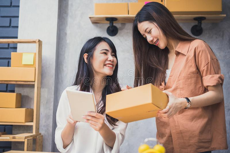 Two young Asian people startup small business entrepreneur SME distribution warehouse with parcel mail box. small  owner home royalty free stock photos