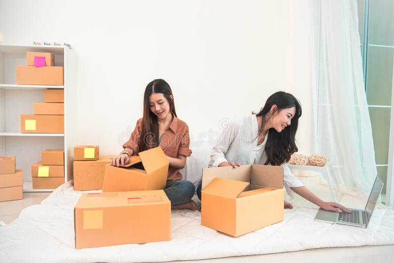 Two young Asian people startup small business entrepreneur SME distribution warehouse with parcel mail box. small  owner home royalty free stock photography