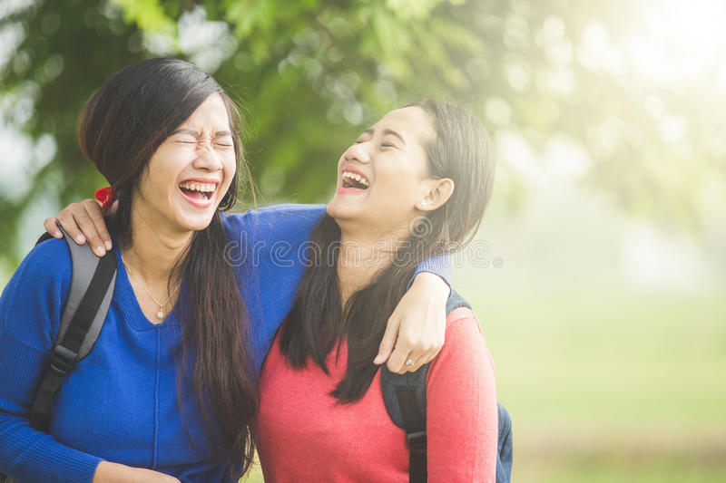 Two young Asian students laugh, joking around together stock photos