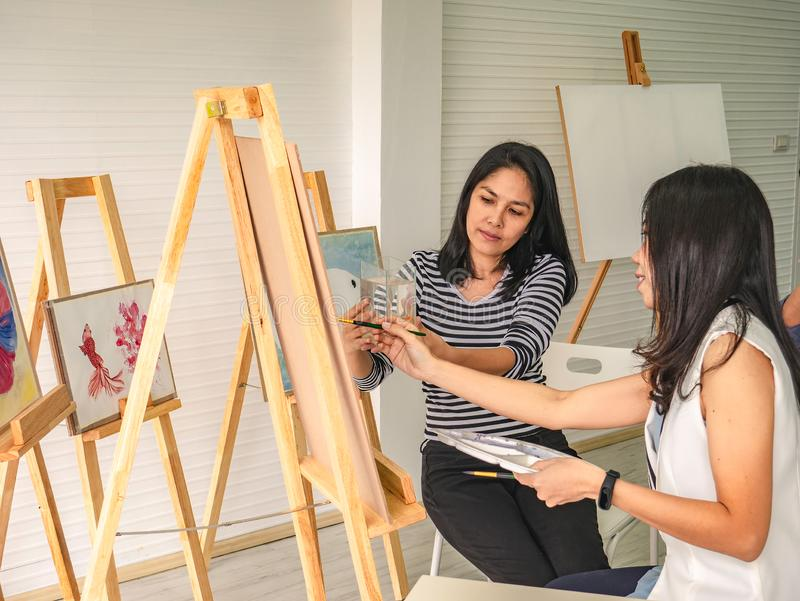 Two young asian woman artist dawning while useing ideas to think and create the best artwork together royalty free stock photography