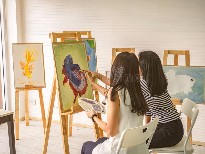 Two young asian woman artist dawning while useing ideas to think and create the best artwork together stock illustration