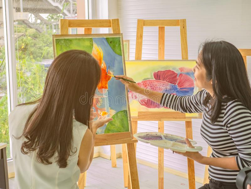 Two young asian woman artist dawning while useing ideas to think and create the best artwork together stock images