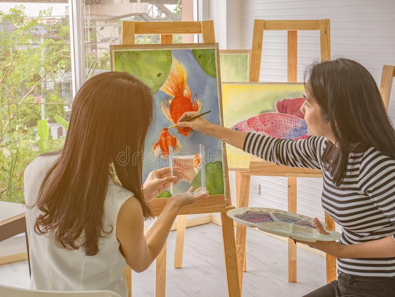 Two young asian woman artist dawning while useing ideas to think and create the best artwork together stock image