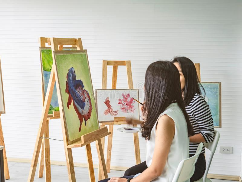 Two young asian woman artist dawning while useing ideas to think and create the best artwork together royalty free stock photo