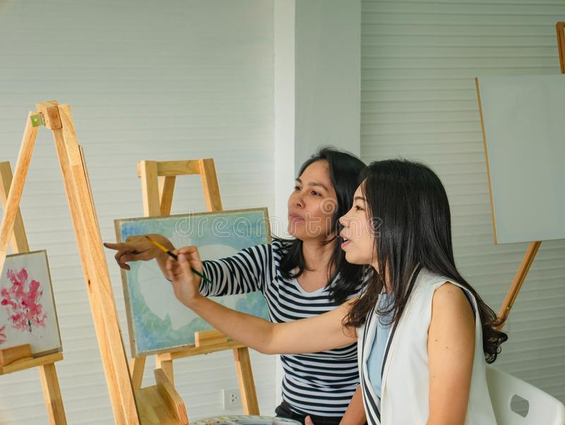 Two young asian woman artist dawning while useing ideas to think and create the best artwork together stock photos