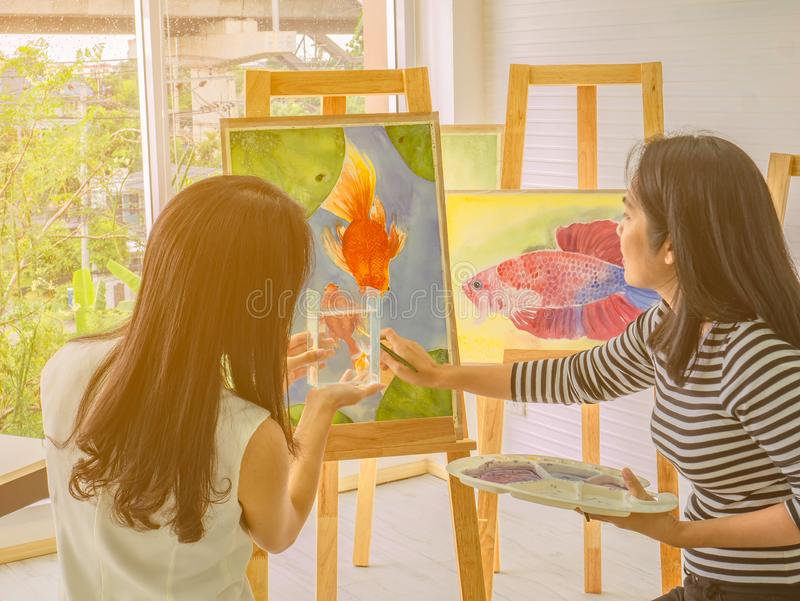 Two young asian woman artist dawning while useing ideas to think and create the best artwork together royalty free stock image