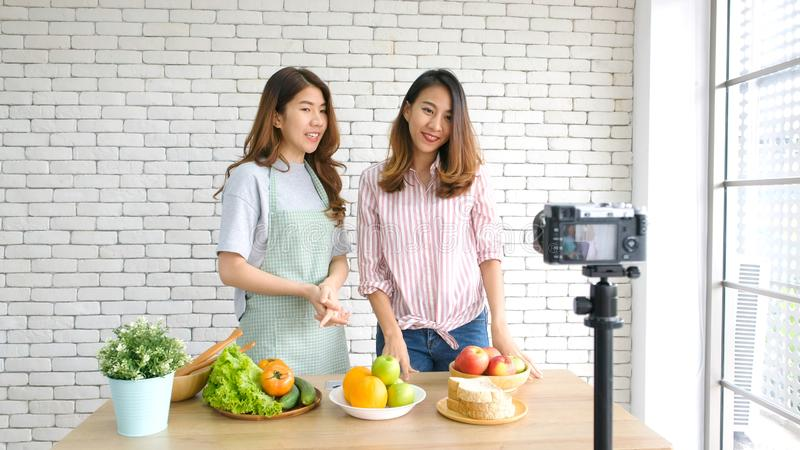 Two young asian women food bloggers talking while recording video with happy moment, vlog concept, people and technology stock photos