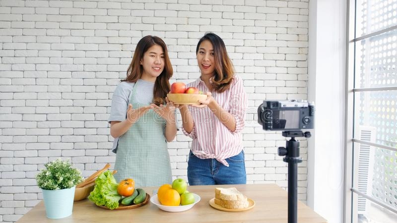 Two young asian women food bloggers talking while recording video with happy moment, vlog concept, people and technology royalty free stock photos