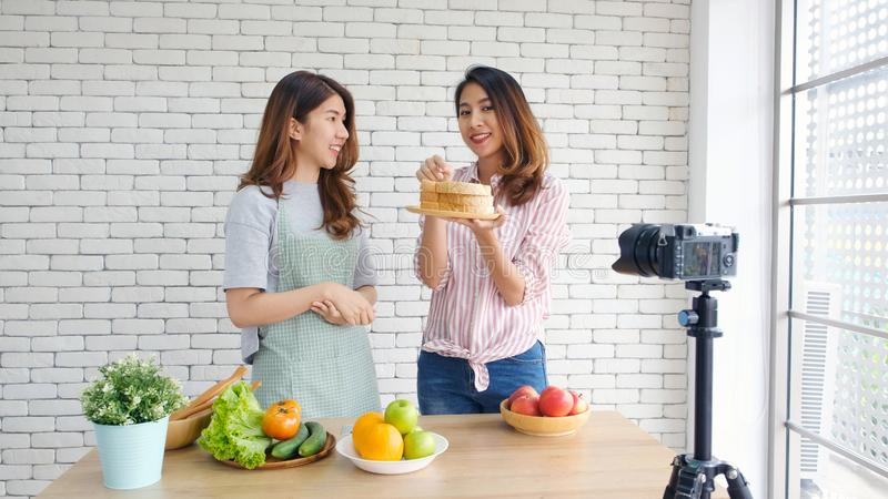 Two young asian women food bloggers talking while recording video with happy moment, vlog concept, people and technology stock photo