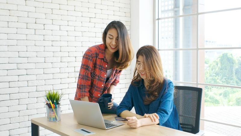 Two young asian women holding credit card and using laptop computer for shopping on line with happiness, business and technology royalty free stock photos